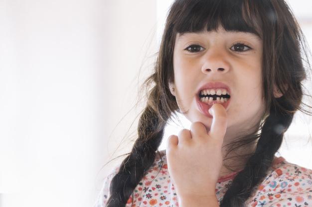 primer-plano-nina-mostrando-sus-dientes-rotos_23-2147824097